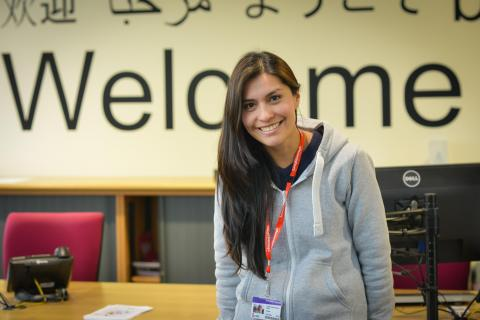 A smiling Loughborough College student sitting on the desk in our new HUB with welcome to Loughborough College on the wall behind